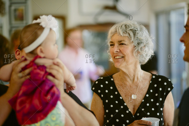 Woman smiling at a baby while at a family party
