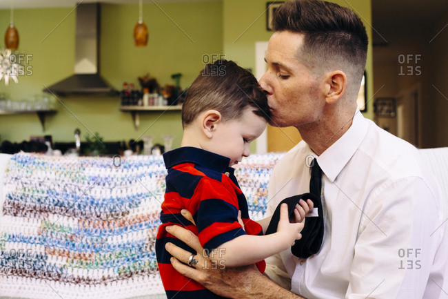 Boy playing with his father's tie while being kissed on the forehead