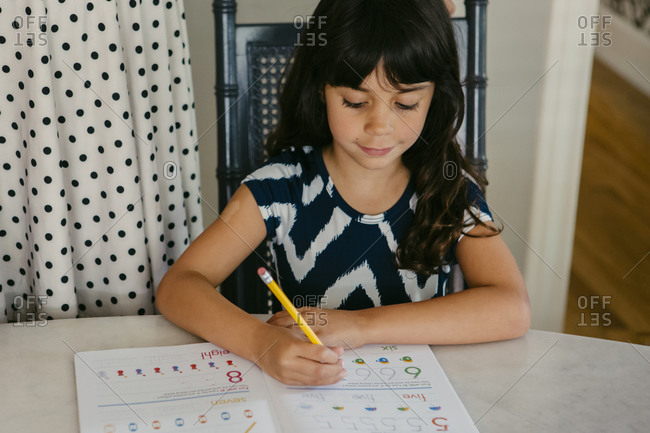 Little girl practicing writing numbers in an activity book