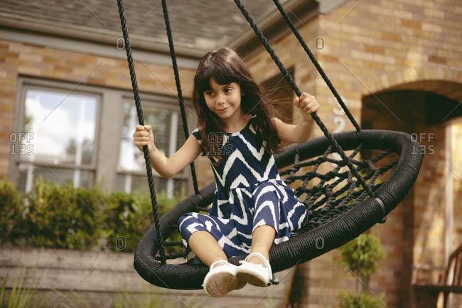 Little girl swinging on a round swing