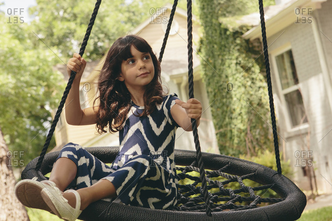 Little girl swinging on a round tree swing
