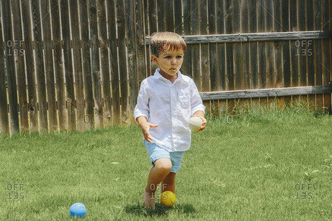 Boy standing in yard with balls