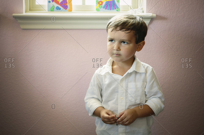 Boy standing against a wall staring