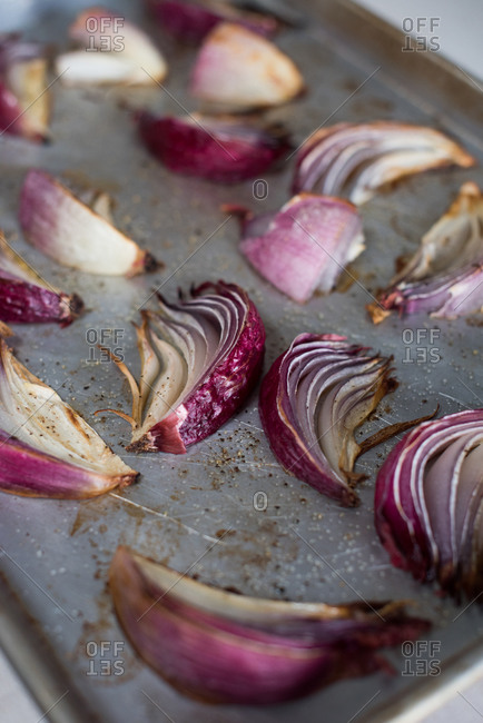 Roasted red onions on a baking sheet