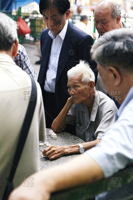 Hong Kong, China - July 22, 2011: A crowd of men playing checkers in a public square