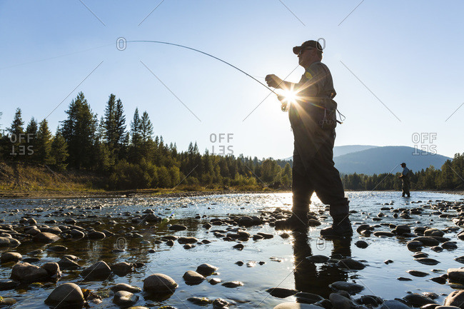 Fly fisherman casting in river