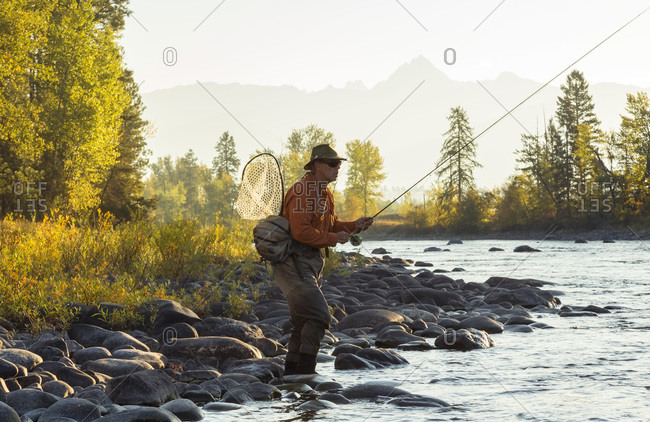 Fly fisherman casting from shore