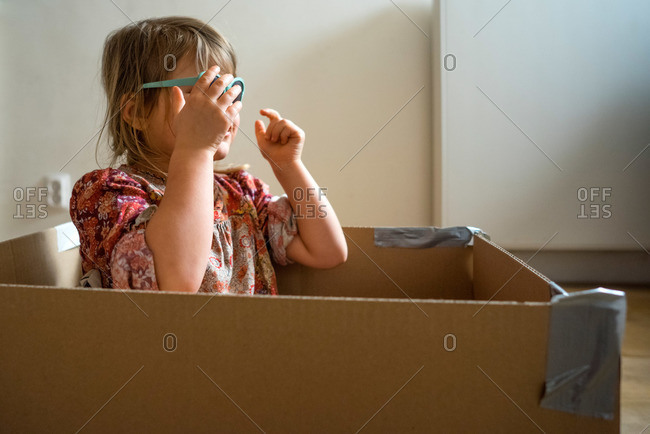 Girl in a box putting on sunglasses