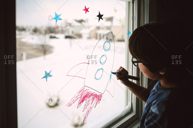 Little boy drawing a rocket on a window