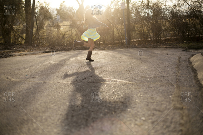 Girl dancing at the end of the street in a hazy light