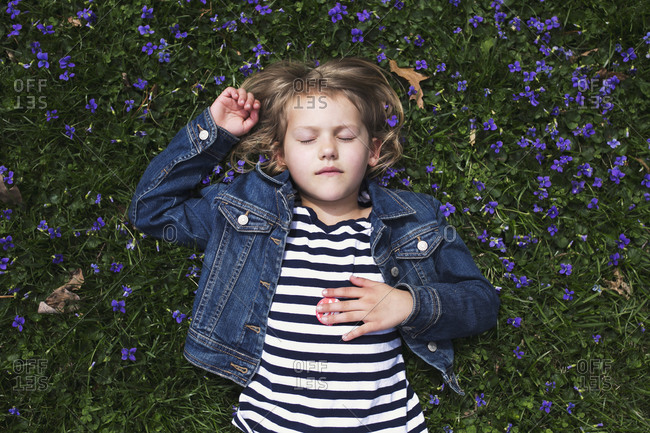 Overhead view of girl lying in grass surrounded by violets