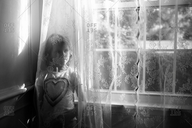 Young girl standing behind lace curtains