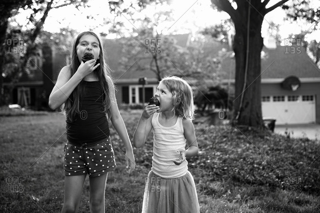 Two girls outside eating cupcakes