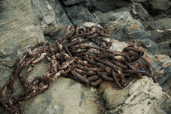Rusty, barnacle covered chain anchored to a rocky outcropping