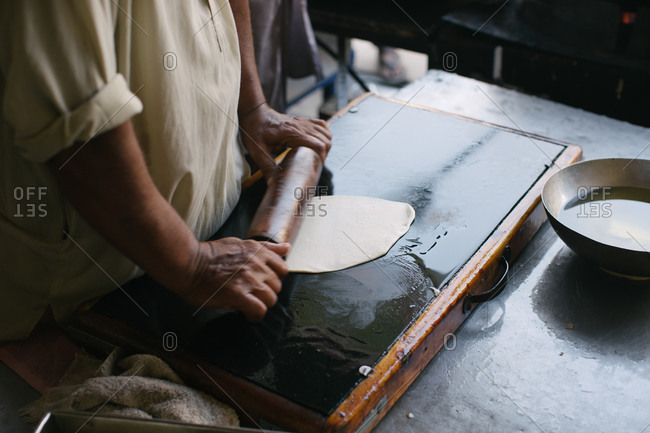 Baker rolling dough on an oiled surface