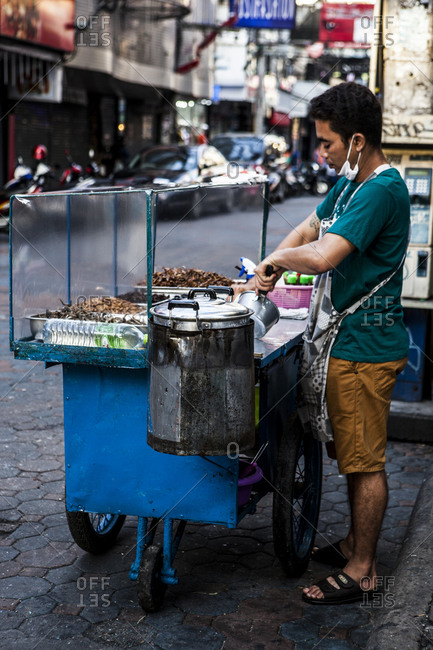Thailand - January 10, 2016: Thai street vendor selling cooked insects from a cart