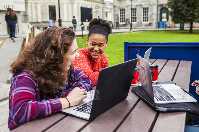 Two college friends laughing while using laptops at outdoor table on campus