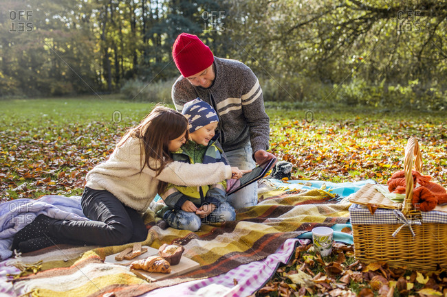 Father showing children tablet computer at autumn picnic