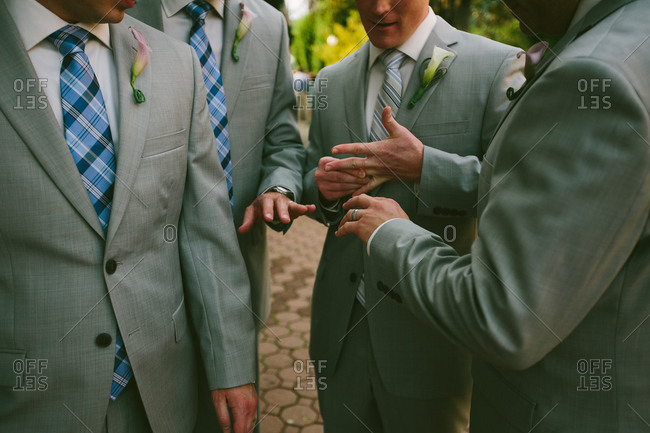 Groomsmen standing around comparing rings at a wedding