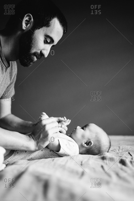 Father playing with his baby daughter on a bed