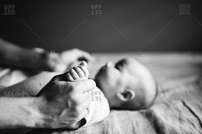 Father holding his baby daughter's hand on a bed