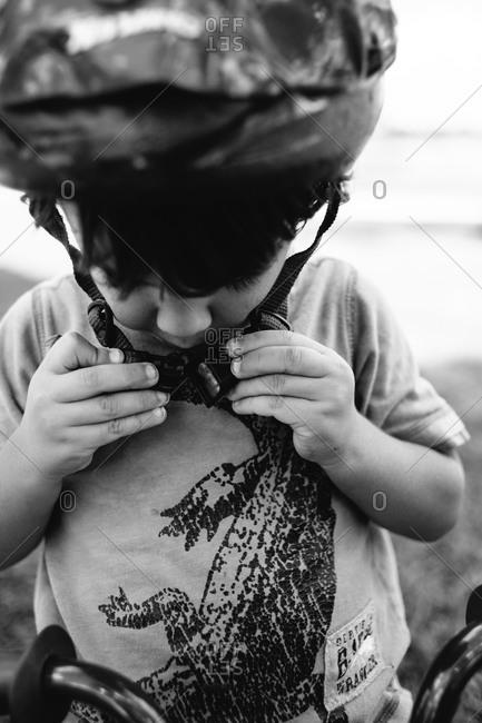 Little boy fastening a bicycle helmet