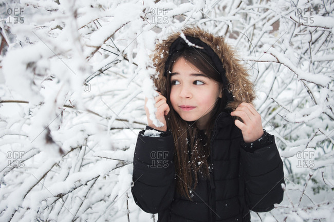 Little girl standing beneath snow-covered branches