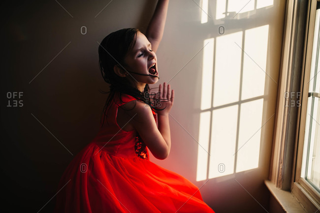 Little girl in a red dress standing by a window yelling