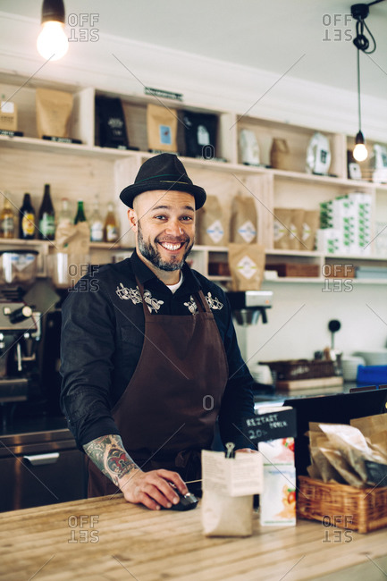 Portrait of happy owner standing at cafe counter