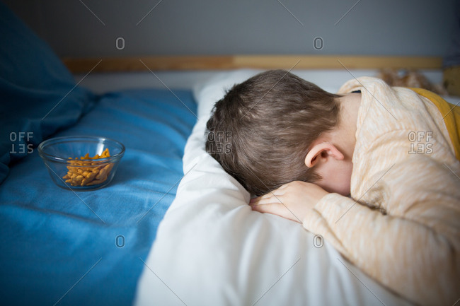 Toddler taking a nap with snack waiting on his bed