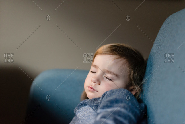 Child curled up on a chair