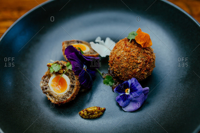Deep fried eggs garnished with purple flowers