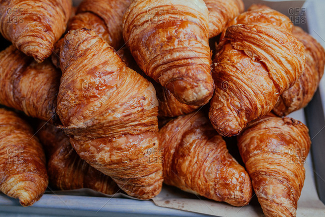 Fresh baked croissants piled on a tray