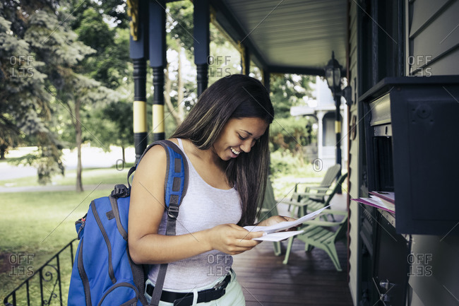 Young woman checking the mail on the front porch