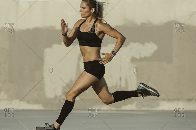 Athletic woman in shorts and a sports bra running outside