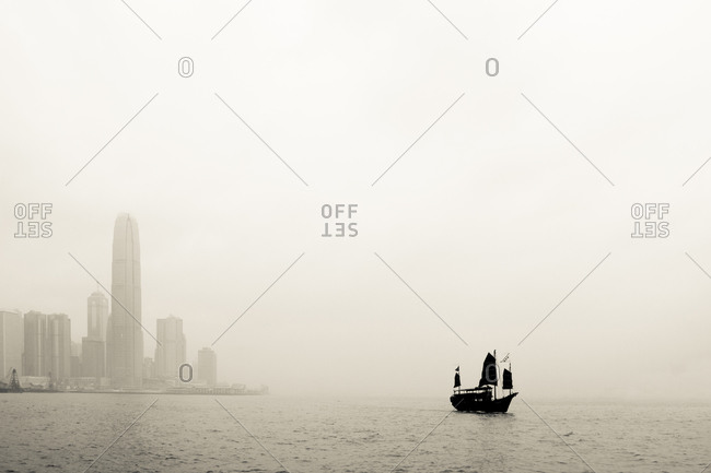 Traditional Chinese junk boat crossing Victoria Harbor in Hong Kong