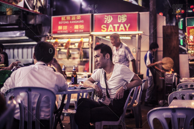 Kuala Lumpur, Malaysia - December 1, 2015: Men eating at a restaurant along Jalan Alor, Kuala Lumpur's famous food street