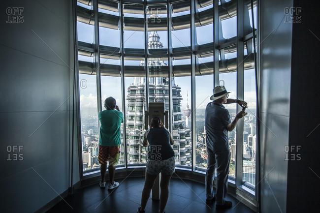 Kuala Lumpur, Malaysia - December 1, 2015: Visitors viewing one of the Petronas Towers in Kuala Lumpur