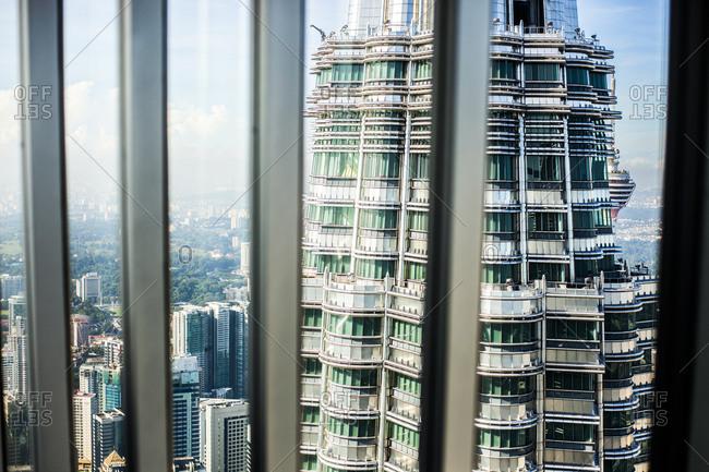 Kuala Lumpur, Malaysia - December 1, 2015: Petronas Towers and Kuala Lumpur skyline seen from the window of a skyscraper