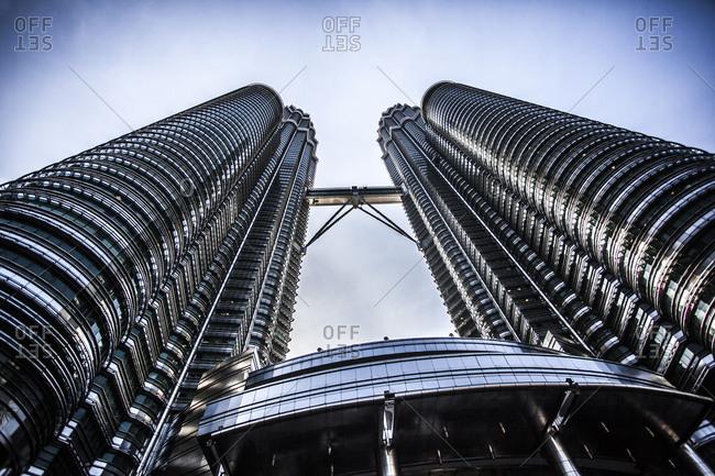 Kuala Lumpur, Malaysia - December 1, 2015: Petronas Towers and skybridge exterior seen from below in Kuala Lumpur