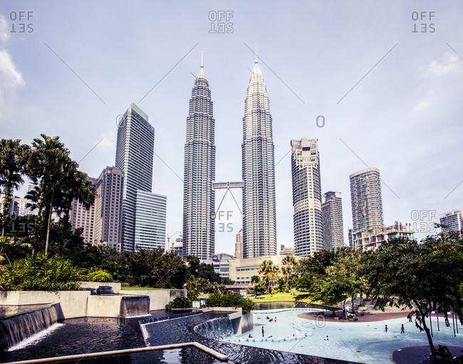 Kuala Lumpur, Malaysia - December 1, 2015: Waterpark and the Kuala Lumpur skyline with Petronas Towers