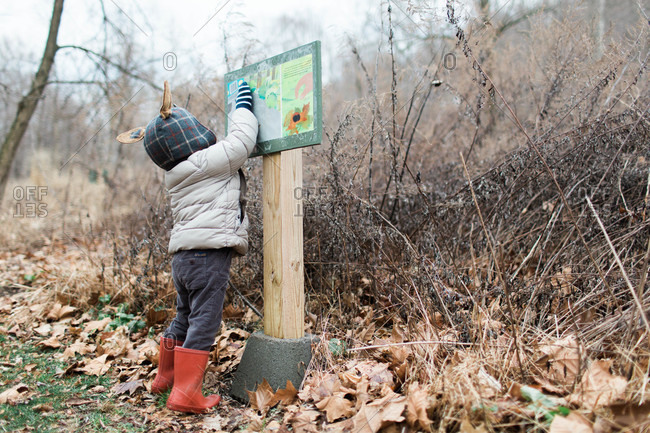Toddler wearing a hat with ears touching a sign at a nature park