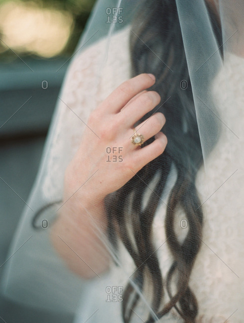 Close up of a bride wearing a veil and a pearl wedding ring