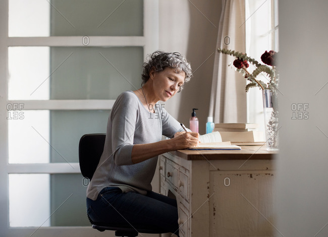 Woman writing in journal at desk