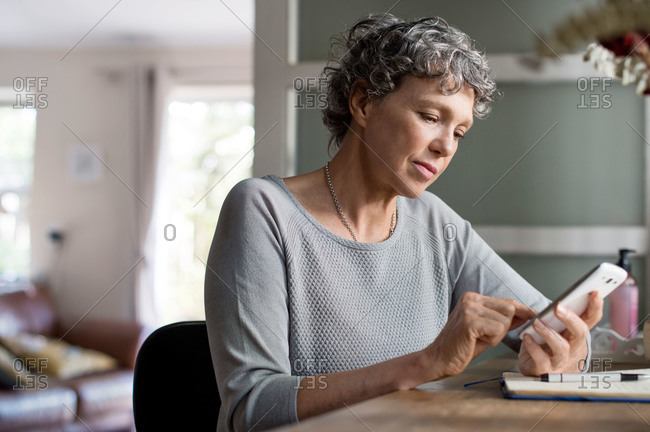 Woman at home desk checking phone