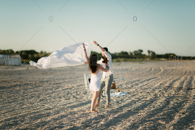 Couple attempts to spread out blanket on windy beach