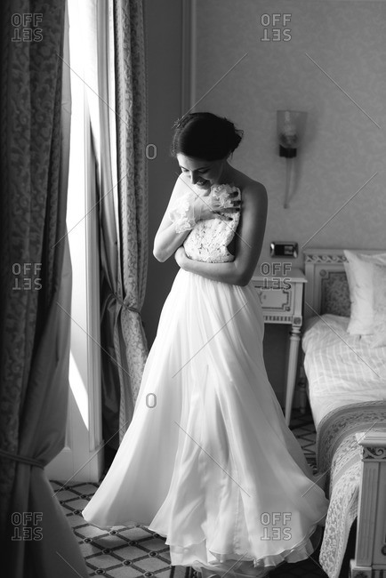 Smiling bride holding dress up against her by hotel room window