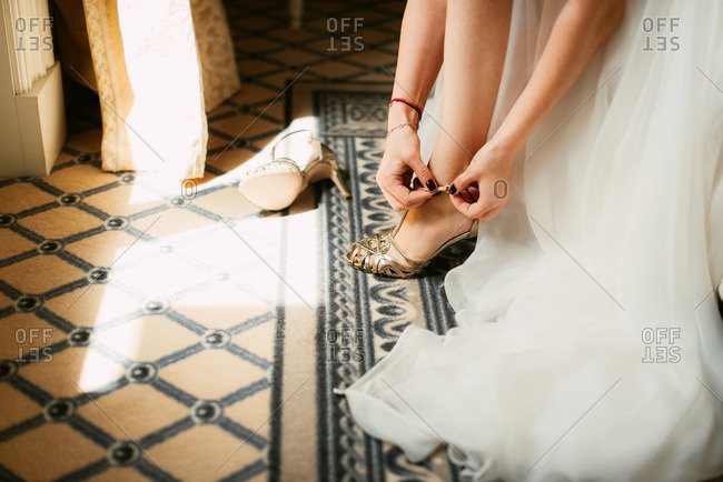 Close-up of bride buckling gold shoe