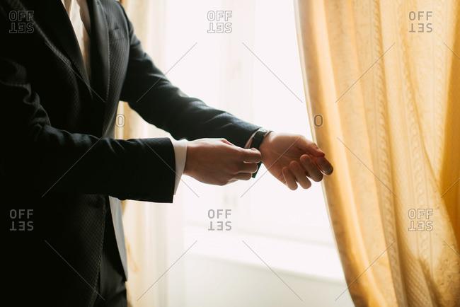 Groom buckling watch around his wrist