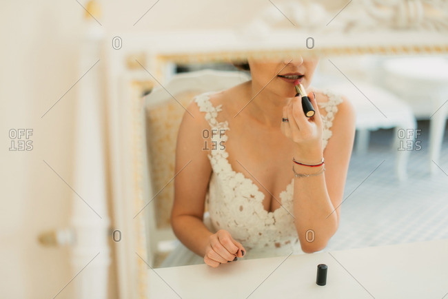 Bride sitting at vanity to apply lipstick